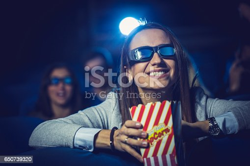 istock Cute girl watching a movie with friends 650739320