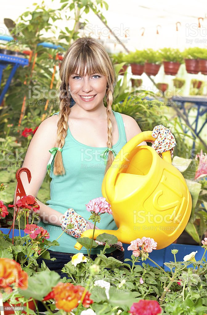 cute girl watering flowers in the greenhouse stock photo