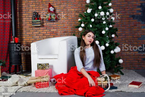 Cute girl wear on warm sweaters, black pants against new year tree with christmas decoration at studio.