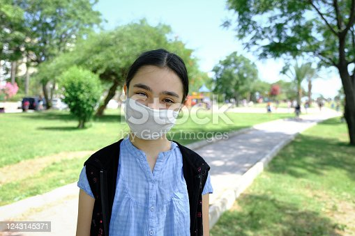 Cute girl wearing a protective mask, her eyes laughing