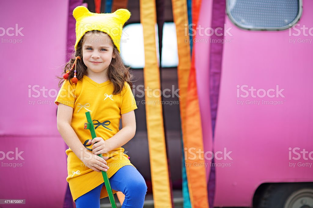 cute girl wearing yellow hat posing against caravan royalty-free stock photo