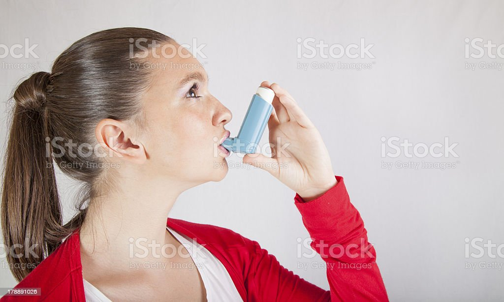 Cute girl with asthma inhaler stock photo