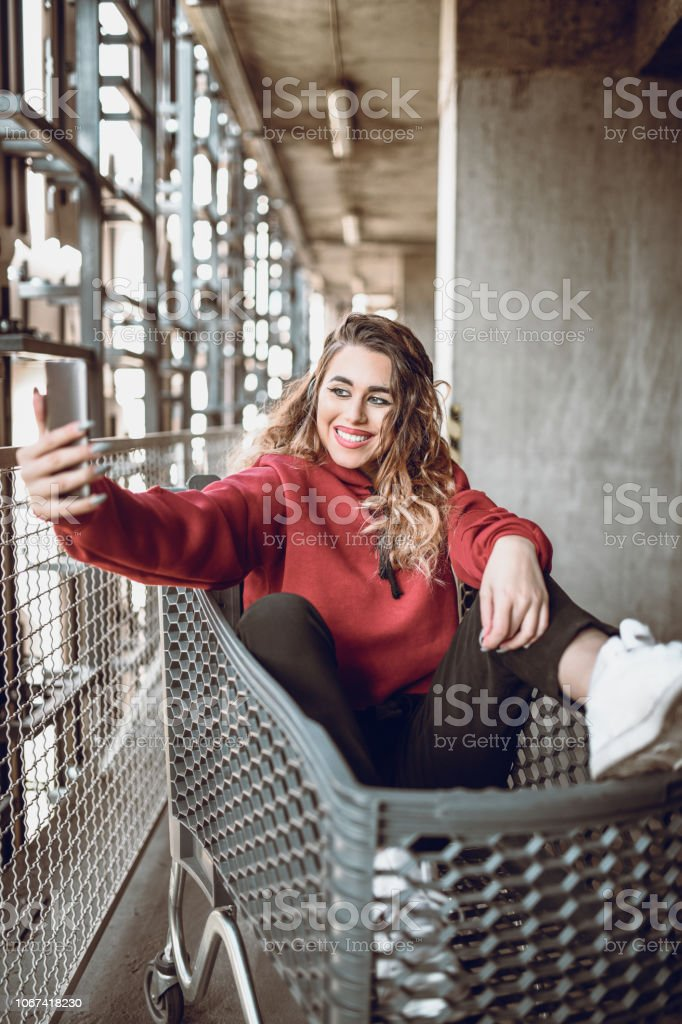 Cute Girl With Curly Hair Is Taking A Selfie On Shopping Cart stock photo
