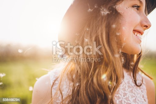 istock Cute girl with dandelion seeds in her hair 538466294
