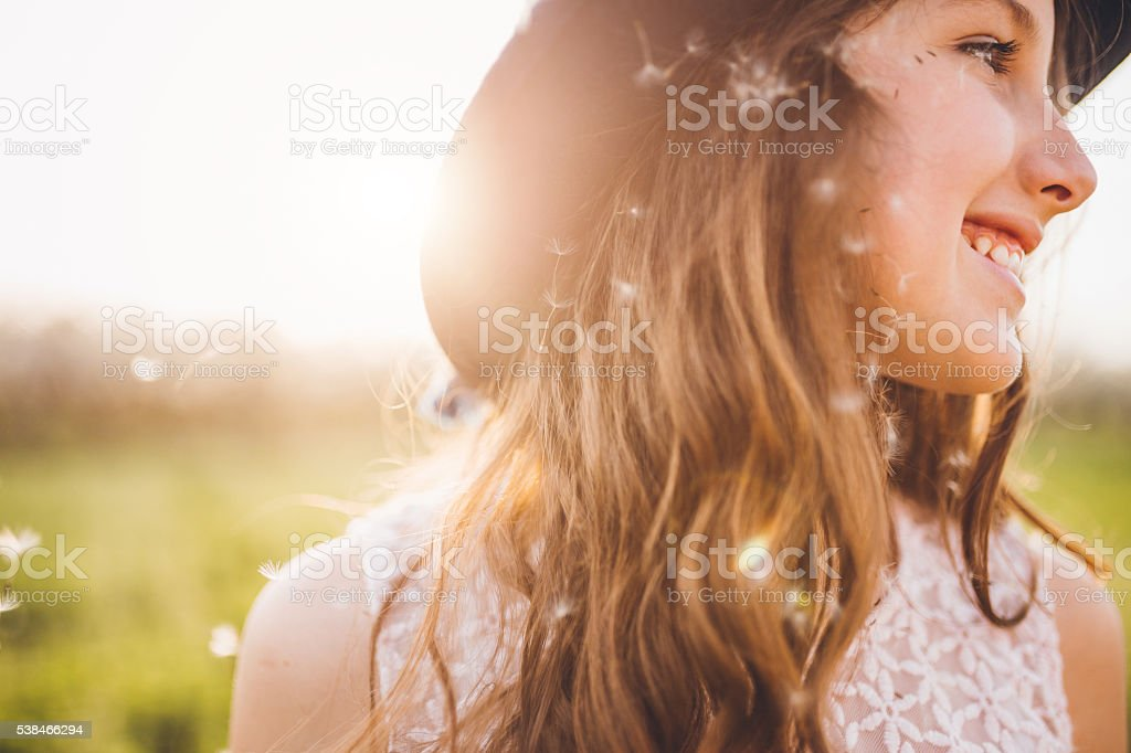 Cute girl with dandelion seeds in her hair stock photo