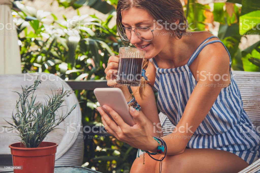 Cute girl with eyeglasses using cellphone  on a terrace. stock photo