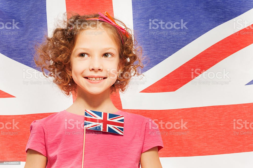 Cute girl with flag, banner of England behind stock photo