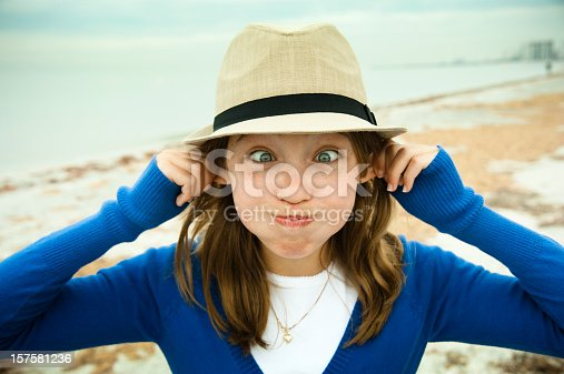 A cute young girl with a panama hat is making a funny face on the beach. She is wearing a royal blue cardigan on a white t-shirt. Hair is mid-long and eyes very blue. This was taken in Clearwater, Florida, Shallow DOP, focus on the face. Horizontal with copy space.