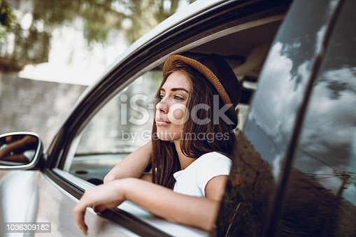 Cute Girl with Hat Sitting In Car and Waiting