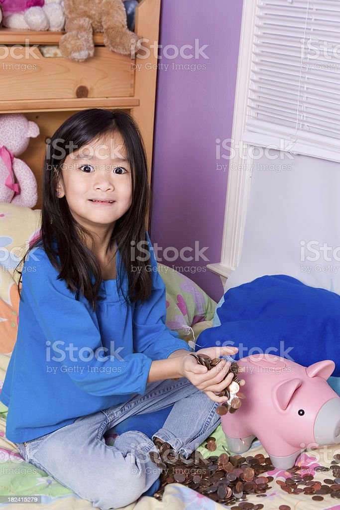 Cute girl with her savings from piggybank royalty-free stock photo