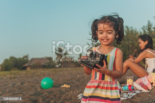 Happy little girl with instant camera at the beach