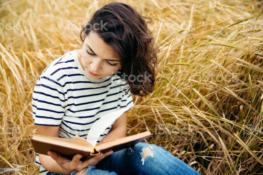 Chica Linda Con El Pelo Castano Loco Leyendo Libro Al Aire Libre En El Campo De Trigo Foto De Stock Y Mas Banco De Imagenes De Adolescente Istock