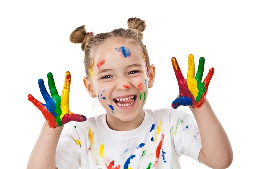 Portrait of a little girl with hands and face covered with multi colored paint and sticking out tongue against white background. The girl is wearing a white shirt also with paint stains. DSRL studio photo taken with Canon EOS 5D Mk II and Canon EF 70-200mm f/2.8L IS II USM Telephoto Zoom Lens