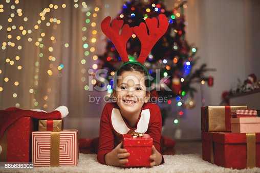 Cute girl with presents and Santa's hat on a Christmas/New Year's Eve