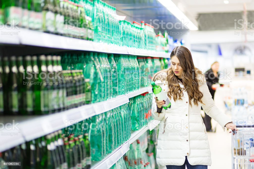Cute girl with shopping cart choosing products stock photo