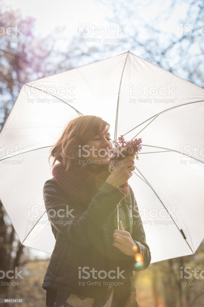Cute girl with white umbrella and flowers enjoying in nature. royalty-free stock photo