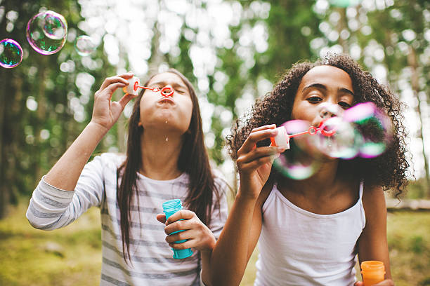 Cute girls blowing bubbles outdoors Cute girls blowing bubbles outdoors pre adolescent child stock pictures, royalty-free photos & images