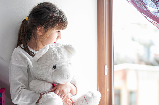 Little cute girl boring at home with her teddy bear