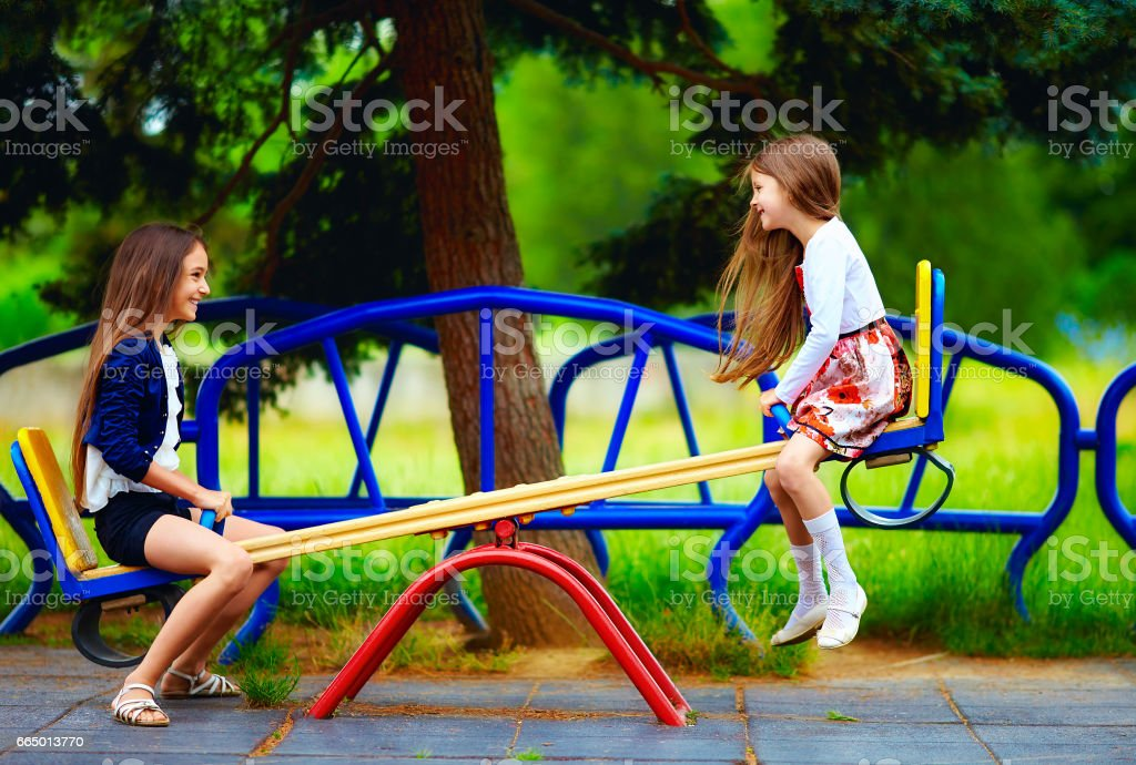 cute girls having fun on seesaw at playground stock photo
