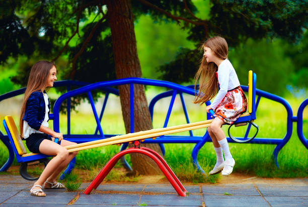 cute girls having fun on seesaw at playground stock photo