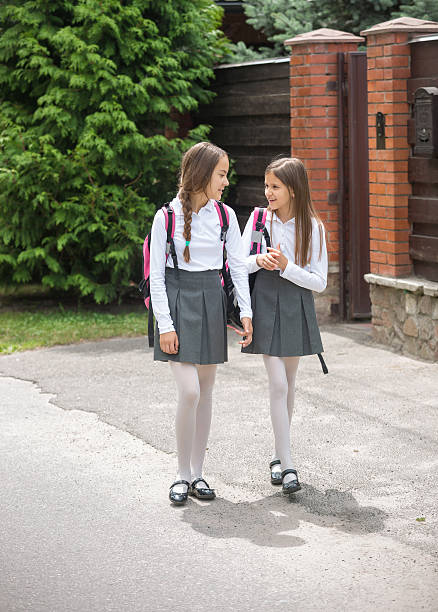 Cute girls in uniform walking to school and chatting stock photo
