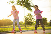 Beautiful twin sisters racing on roller skates in public park