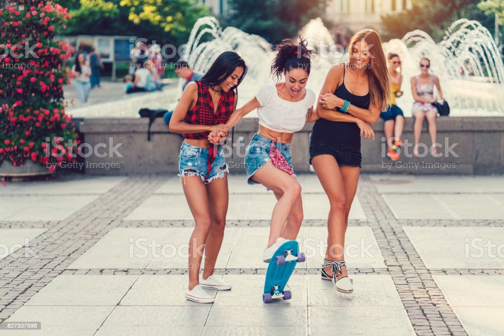 Cute girls skateboarding in the city stock photo