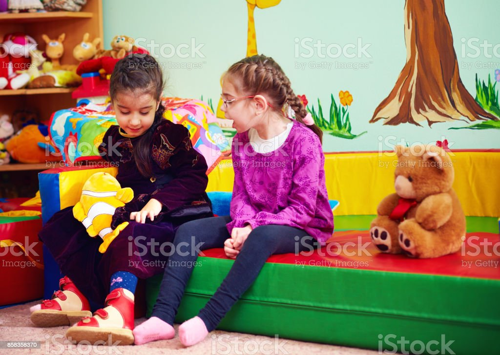 cute girls talking and playing in kindergarten for kids with special needs stock photo