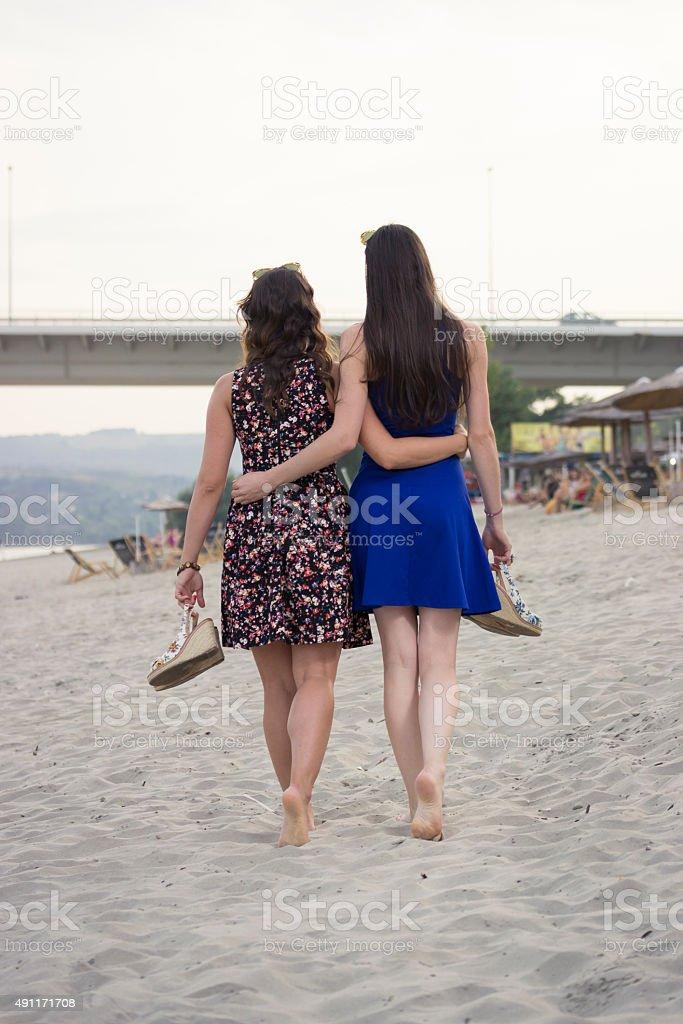 Cute girls walking on beach, hugged. Shot from behind, back. stock photo