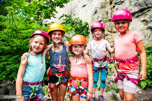 Five strong, confident and athletic young girls pose in front of a mountain climbing rock face.  A beautiful, positive portrait of elementary aged girls at a summer climbing camp.