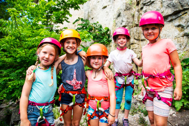 A cute group of strong, confident girls at a summer rock climbing camp. stock photo