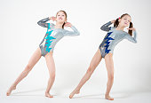 Two young girls performing gymnastic pose on a white background
