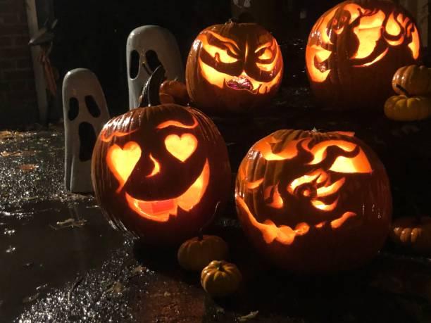 Cute Halloween Jack o'lantern pumpkins on rainy Halloween night stock photo