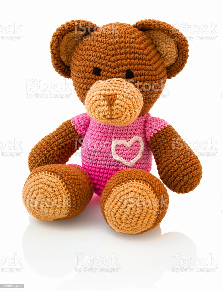 Cute handmade crochet bear doll isolated on white background with shadow reflection. Playful crochet brown pinky bear sitting on white underlay. Knitted bear. stock photo