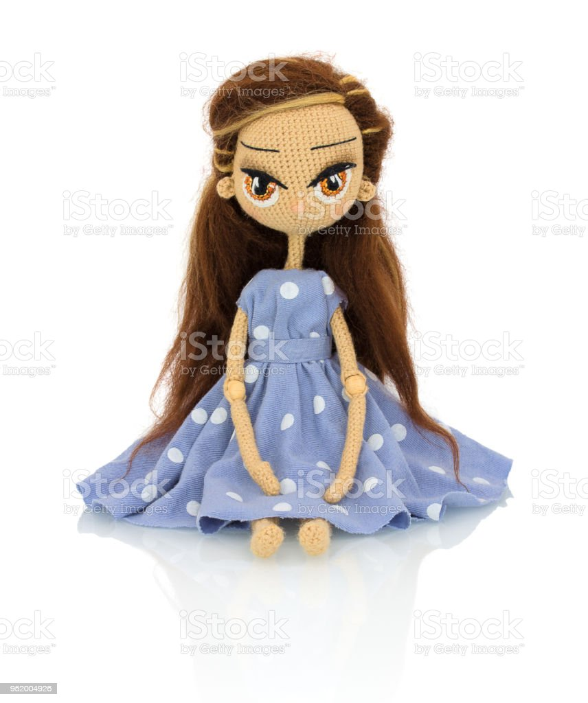 Cute handmade crochet doll with speckled blue dress isolated on white background with shadow reflection. Playful crochet brown hair doll sitting on white underlay. Knitted doll. stock photo