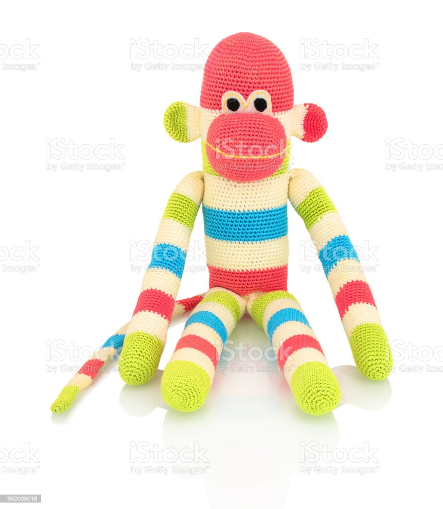 Cute handmade crochet monkey doll isolated on white background with shadow reflection. Playful crochet green pink blue white monkey sitting on white underlay. Knitted ape. stock photo