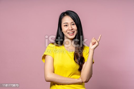 Cute happy asian woman in yellow casual shirt looking at camera, smiling and pointing finger to side on pink studio background for texting or advertise.