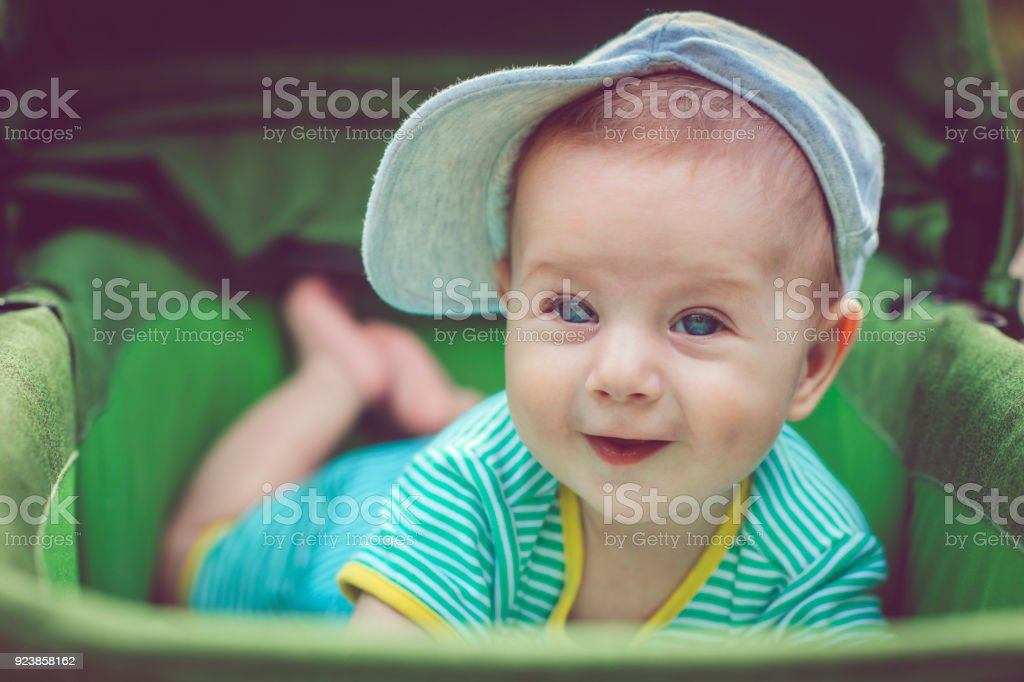 Cute happy baby boy in carriage Cute 5 months baby boy playing with legs in a summer day outdoors 0-11 Months Stock Photo