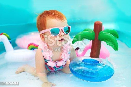 cute happy baby girl having fun in kid pool, summer vacation