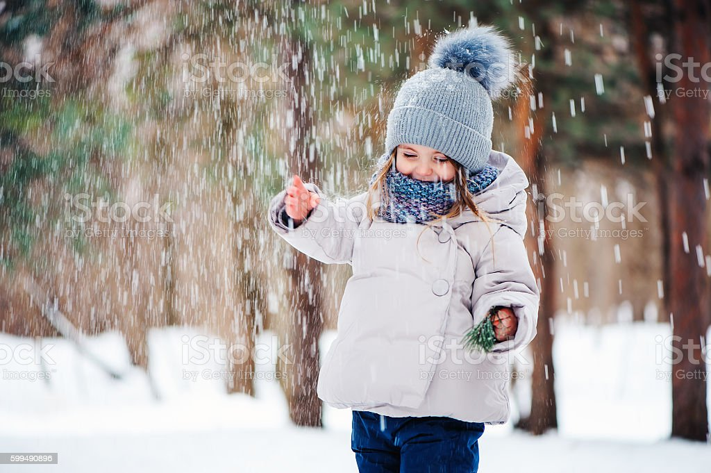 cute happy baby girl playing in snowy winter forest stock photo