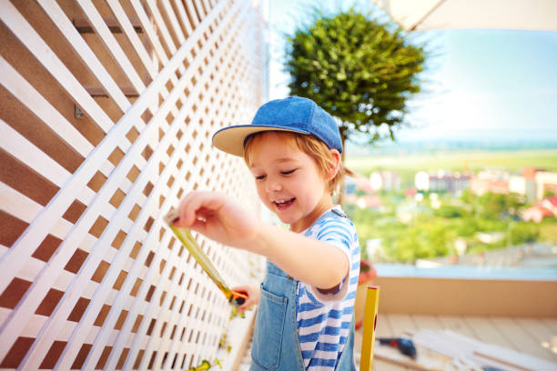 cute happy boy helping to set up a trellis on patio stock photo