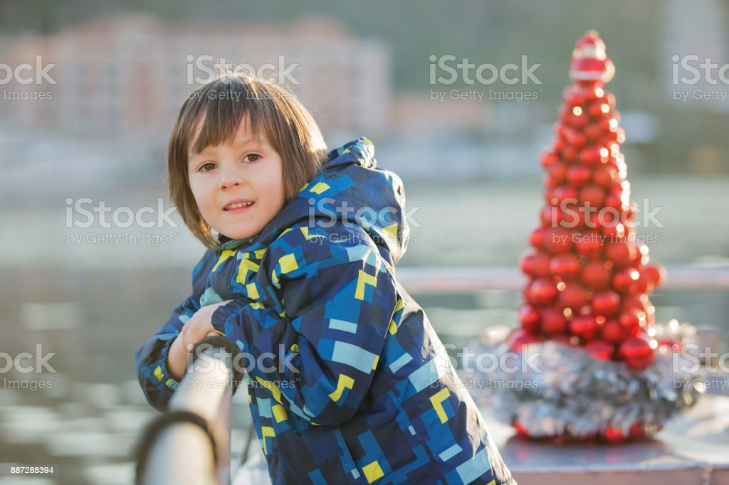 Cute happy child, traveling on a boat on a lake during Christmas stock photo