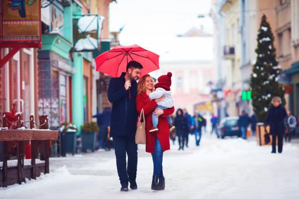 niedliche glückliche familie zu fuß entlang der verschneiten stadt straße, winterurlaub - festliche babymode junge stock-fotos und bilder