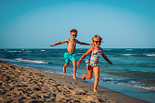 cute happy girl and boy running on beach, family have fun at sea