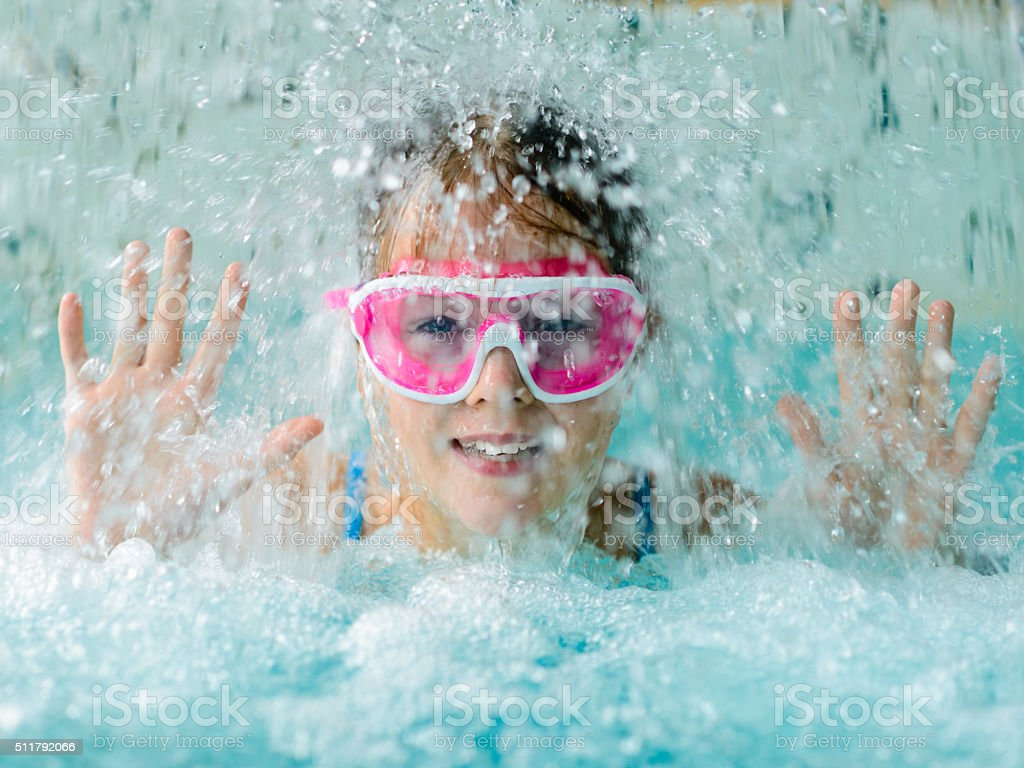Cute happy girl in pink goggles mask in the pool stock photo