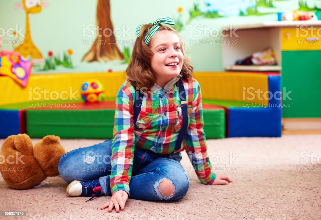 cute happy girl playing in kindergarten for kids with special needs - foto stock