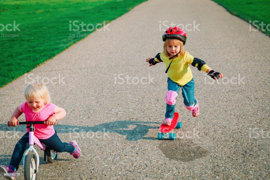 andar bonitos meninas felizes em bicicleta e skate - Foto de stock de Amizade royalty-free