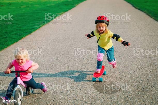 Foto de Andar Bonitos Meninas Felizes Em Bicicleta E Skate e mais fotos de stock de Amizade