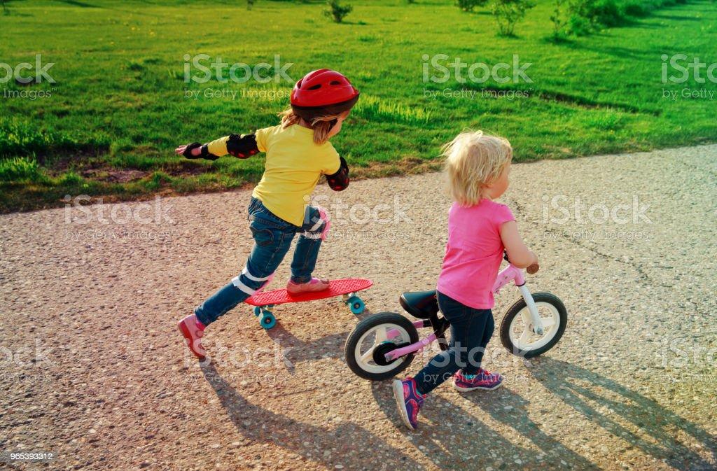 cute happy girls on bike and skateboard ride zbiór zdjęć royalty-free