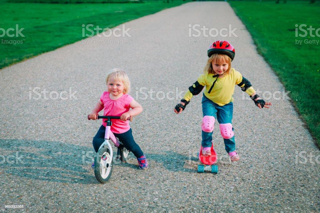 자전거와 스케이트 보드에 귀여운 행복 한 여자를 타고 - 로열티 프리 가족 스톡 사진